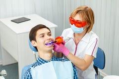Όμορφη μεταχείρηση οδοντιάτρων γυναικών υπομονετικά δόντια οδοντικό σε offic Στοκ Φωτογραφία