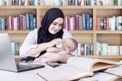 Όμορφη μητέρα που εργάζεται ταΐζοντας το μωρό της στοκ εικόνα με δικαίωμα ελεύθερης χρήσης