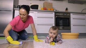 Όμορφη μητέρα στα γόνατα που πλένουν το πάτωμα κοντά στο μωρό φιλμ μικρού μήκους