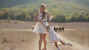 Όμορφη μητέρα στο ελαφρύ φόρεμα που κρατά την λίγα απόθεμα βίντεο