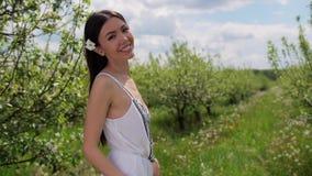 Όμορφη μικτή γυναίκα φυλών που περπατά στον οπωρώνα μήλων φιλμ μικρού μήκους