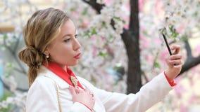 Όμορφη μοντέρνη γυναίκα με το επαγγελματικές makeup και την τρίχα που κάνουν selfie ή ιστορίες στο κινητό τηλέφωνο για το instagr απόθεμα βίντεο