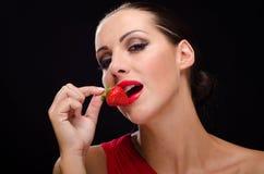 Όμορφη, μοντέρνη γυναίκα που τρώει μια φράουλα Στοκ φωτογραφία με δικαίωμα ελεύθερης χρήσης