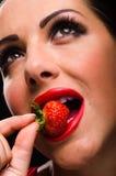 Όμορφη, μοντέρνη γυναίκα που τρώει μια φράουλα Στοκ εικόνα με δικαίωμα ελεύθερης χρήσης