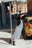 Όμορφη μοντέρνη γυναικεία τοποθέτηση στην παλαιά οδό Στοκ Εικόνα