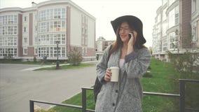 Όμορφη, μοντέρνη, επιχειρησιακή γυναίκα στο καπέλο και γυαλιά που μιλούν στο τηλέφωνο υπαίθριο φιλμ μικρού μήκους