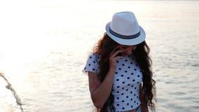 Όμορφη μοντέρνη ευτυχής μοντέρνη νέα γυναίκα που μιλά στο τηλέφωνο, που περπατά στην άμμο κατά μήκος της παραλίας Όμορφο κορίτσι απόθεμα βίντεο