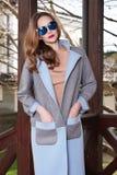 Όμορφη μοντέρνη νέα επιχειρησιακή γυναίκα που φορά μέσα; rimson παλτό και γυαλιά ηλίου φθινοπώρου με το hairdo και makeup περπάτη Στοκ Εικόνες