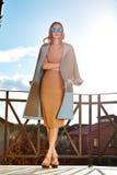 Όμορφη μοντέρνη νέα επιχειρησιακή γυναίκα που φορά μέσα; rimson παλτό και γυαλιά ηλίου φθινοπώρου με το hairdo και makeup περπάτη Στοκ Εικόνα
