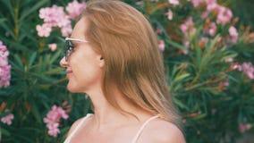 Όμορφη μοντέρνη ξανθή γυναίκα στα γυαλιά ηλίου που περπατά στο πάρκο με τους ανθίζοντας θάμνους oleander τα λουλούδια απεικονίζον φιλμ μικρού μήκους