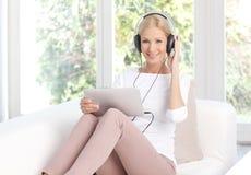 Όμορφη μουσική ακούσματος γυναικών στο σπίτι Στοκ εικόνα με δικαίωμα ελεύθερης χρήσης