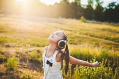 Όμορφη μουσική ακούσματος κοριτσιών και χαμόγελο Στοκ εικόνα με δικαίωμα ελεύθερης χρήσης