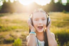 Όμορφη μουσική ακούσματος κοριτσιών με τα ακουστικά και τραγούδι Στοκ Εικόνες
