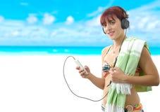 Όμορφη μουσική ακούσματος κοριτσιών με το smartphone της στην παραλία Στοκ Φωτογραφίες