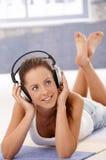 Όμορφη μουσική ακούσματος κοριτσιών που βάζει στο πάτωμα Στοκ εικόνες με δικαίωμα ελεύθερης χρήσης
