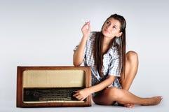 Όμορφη μουσική ακούσματος κοριτσιών σε ραδιο και σκέψη Στοκ φωτογραφία με δικαίωμα ελεύθερης χρήσης