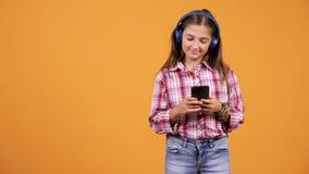 Όμορφη μουσική ακούσματος νέων κοριτσιών κοιτάζοντας στο smartphone φιλμ μικρού μήκους