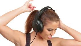 Όμορφη μουσική γυναικείου ακούσματος στα μεγάλα ακουστικά, που εξετάζουν τη κάμερα απόθεμα βίντεο