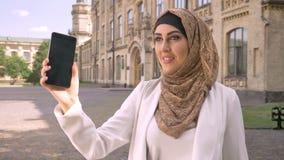 Όμορφη μουσουλμανική επιχειρησιακή γυναίκα στο hijab που έχει την τηλεοπτική συνομιλία μέσω του τηλεφώνου, που στέκεται στην οδό  απόθεμα βίντεο