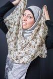 Όμορφη μουσουλμανική γυναίκα που δοκιμάζει το ζωηρόχρωμο μαντίλι Στοκ φωτογραφία με δικαίωμα ελεύθερης χρήσης