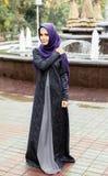 Όμορφη μουσουλμανική γυναίκα στο σύγχρονο ισλαμικό περίπατο φορεμάτων σε ένα πάρκο πόλεων Στοκ Εικόνα