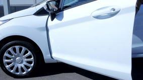 Όμορφη μπροστινή πόρτα αυτοκινήτων νεαρών άνδρων ανοίγοντας που ξεπερνά το άσπρο σύγχρονο ολοκαίνουργιο αυτοκινητικό όχημα φιλμ μικρού μήκους
