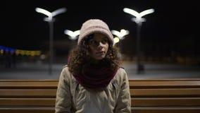 Όμορφη μόνη τη νύχτα στάση λεωφορείου καθίσματος κοριτσιών, πρόγραμμα ξεφυλλίσματος στη συσκευή φιλμ μικρού μήκους