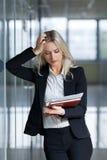 Όμορφη νέαη επιχειρηματίας και που φαίνεται έγγραφα στο γραφείο στοκ φωτογραφίες με δικαίωμα ελεύθερης χρήσης