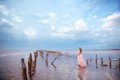 Όμορφη νέα έγκυος γυναίκα που απολαμβάνει τον ήλιο στη ρόδινη λίμνη στοκ εικόνα