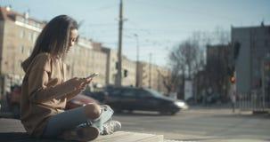 Όμορφη νέα δακτυλογράφηση γυναικών στο τηλέφωνο κατά τη διάρκεια της ηλιόλουστης ημέρας απόθεμα βίντεο