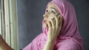 Όμορφη νέα αραβική γυναίκα που υπερασπίζεται ένα παράθυρο και που μιλά στο τηλέφωνο κυττάρων απόθεμα βίντεο