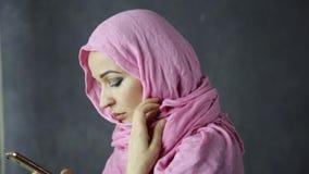 Όμορφη νέα αραβική μουσουλμανική γυναίκα στο ρόδινο hijab που μιλά στο τηλέφωνο κυττάρων απόθεμα βίντεο