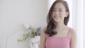 Όμορφη νέα ασιατική γυναίκα πορτρέτου κινηματογραφήσεων σε πρώτο πλάνο με το χαμόγελο και το γέλιο στην κρεβατοκάμαρα, κορίτσι πο απόθεμα βίντεο