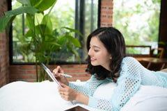 Όμορφη νέα ασιατική γυναίκα που βάζει στο κρεβάτι και που γράφει ένα ημερολόγιο στοκ φωτογραφία