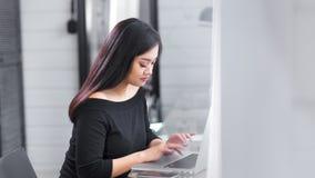 Όμορφη νέα ασιατική δακτυλογράφηση επιχειρηματιών στο πληκτρολόγιο που χρησιμοποιεί το lap-top στην πλάγια όψη γραφείων απόθεμα βίντεο