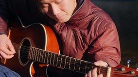 Όμορφη νέα ασιατική κιθάρα παιχνιδιού ατόμων στην ακτή του δασικού ποταμού στην ανατολή Misty ομίχλη της Dawn στο υπόβαθρο απόθεμα βίντεο