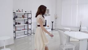Όμορφη νέα γυναίκα κινήσεις στις μπεζ φορεμάτων στο εσωτερικό στο καθιστικό σε σε αργή κίνηση Σε αργή κίνηση οικογενειακή κατοικί απόθεμα βίντεο