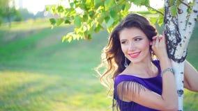 Όμορφη νέα γυναίκα κοντά στα δέντρα σημύδων στο πάρκο απόθεμα βίντεο