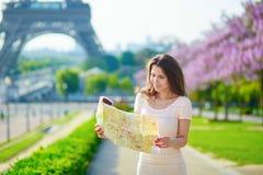 Όμορφη νέα γυναίκα κοντά στον πύργο του Άιφελ στο Παρίσι, που εξετάζει το χάρτη πόλεων Στοκ Φωτογραφίες