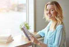 Όμορφη νέα γυναίκα κοντά στο παράθυρο που κρατά ένα βιβλίο εξετάζοντας τη κάμερα στον καφέ Στοκ Φωτογραφίες