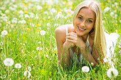 Όμορφη νέα γυναίκα μεταξύ των λουλουδιών Στοκ Φωτογραφίες