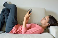 Όμορφη νέα γυναίκα με τα ακουστικά που χαλαρώνει στον καναπέ, ακούει τη μουσική χρησιμοποιώντας ένα έξυπνους τηλέφωνο, μια ψύχρα  Στοκ φωτογραφία με δικαίωμα ελεύθερης χρήσης