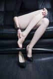 Όμορφη νέα γυναίκα με τα μακριά πόδια στο κομπινεζόν απομονωμένο λευκό πόνου ποδιών Στοκ εικόνα με δικαίωμα ελεύθερης χρήσης