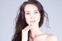 Όμορφη νέα γυναίκα με τα μεγάλα μπλε μάτια και σγουρή τρίχα σχετικά με τα χείλια όμορφη γυναίκα προσώπου Στοκ Εικόνες