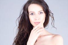 Όμορφη νέα γυναίκα με τα μεγάλα μπλε μάτια και τη σγουρή τρίχα που χαμογελά και σχετικά με τα χείλια όμορφη γυναίκα προσώπου Στοκ Εικόνες
