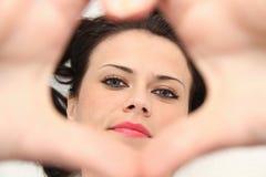 Όμορφη νέα γυναίκα με τα μπλε μάτια που κατασκευάζουν την καρδιά των δάχτυλων Στοκ Εικόνες