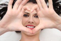 Όμορφη νέα γυναίκα με τα μπλε μάτια που κατασκευάζουν την καρδιά των δάχτυλων Στοκ εικόνα με δικαίωμα ελεύθερης χρήσης