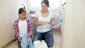 Όμορφη νέα γυναίκα με τα οικιακά έφηβη κόρη doung στο πλυντήριο απόθεμα βίντεο