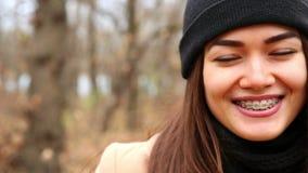 Όμορφη νέα γυναίκα με τα υποστηρίγματα στα δόντια που παρουσιάζουν συγκινήσεις, που χαμογελούν το φθινόπωρο φιλμ μικρού μήκους
