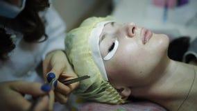 Όμορφη νέα γυναίκα με την επέκταση eyelash Μάτι γυναικών με τα μακροχρόνια eyelashes Επέκταση Beautician eyelash για τις νεολαίες φιλμ μικρού μήκους